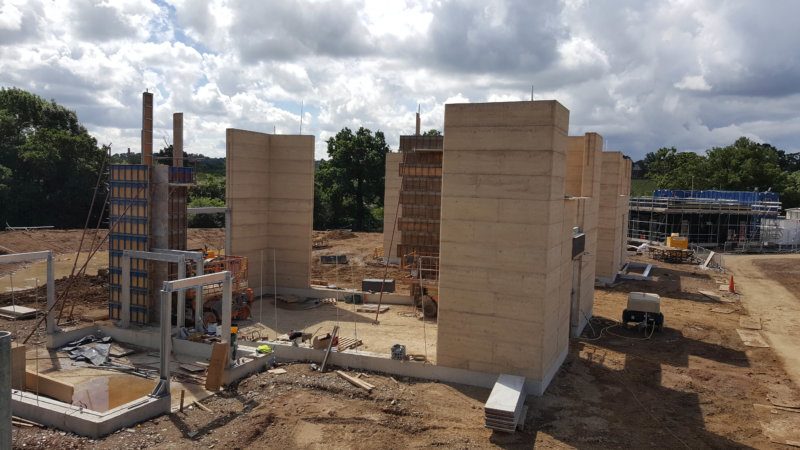 Rammed earth walls under construction.